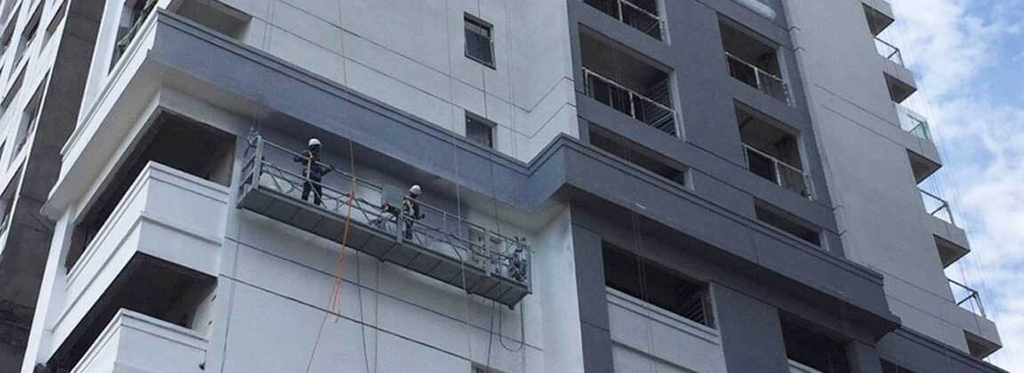The exterior wall of the DI RIVIERA high-rise building in Cambodia is painted with like stone paint. Workers are hanging and spraying ADD STONE like stone paint.